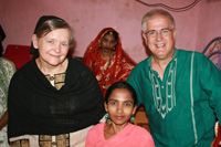 We pose with our helper on the bed in the one room dwelling.
