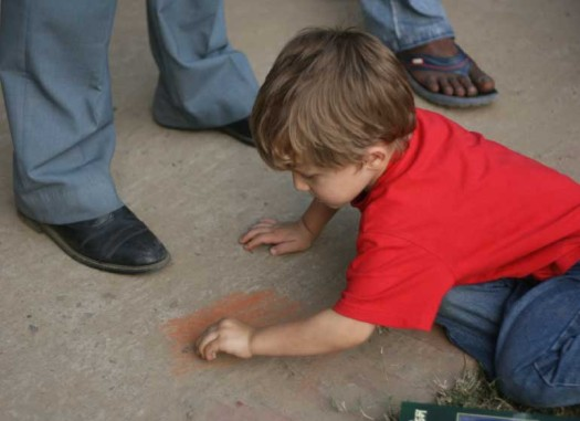Here is Riley drawing on sidewalk with a piece of a brick oblivious to the soccer game.