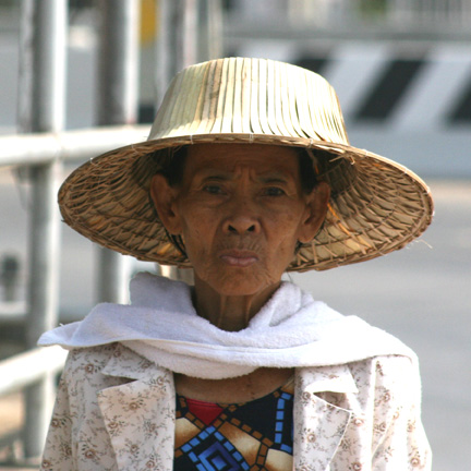 Lady beating the heat with a hat.