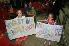 Katriel and Moriah Holding up signs for their Aunt, Uncle and Cousins!