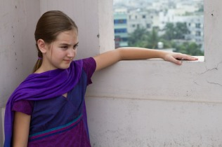 Wearing purple 3-piece and looking out across the city of Dhaka.