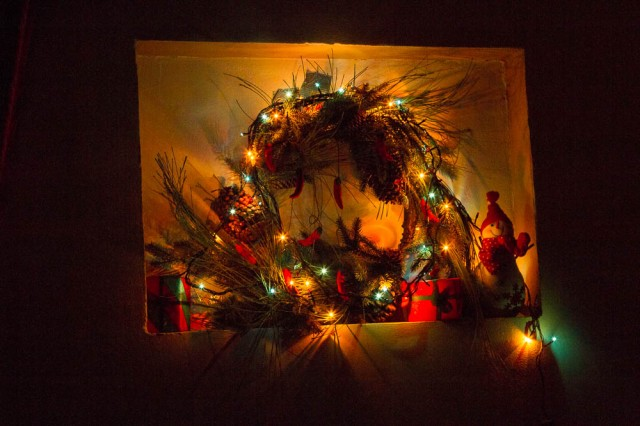 A wreath with lights wrapped around it. This is in our living room!