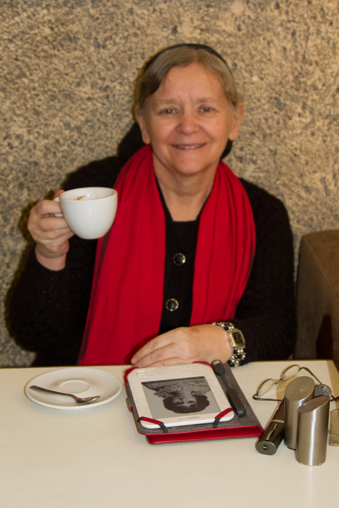 Happy with her Americano coffee while reading on her Kindle!